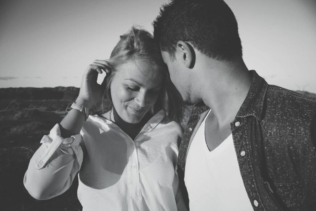 女性が男性の前で 髪を触る